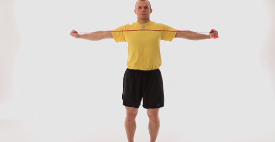 man standing with arms stretched out at shoulder height